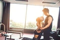 Metta in mostra la ragazza che fa gli esercizi del peso che lavorano con le teste di legno pesanti h Immagine Stock Libera da Diritti