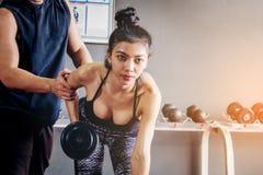 Metta in mostra la ragazza che fa gli esercizi del peso che lavorano con le teste di legno pesanti h Immagini Stock Libere da Diritti