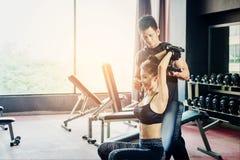 Metta in mostra la ragazza che fa gli esercizi del peso che lavorano con le teste di legno pesanti h Fotografia Stock