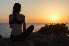 Metta in mostra la ragazza che medita dal mare al tramonto Fotografia Stock