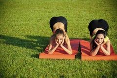 Metta in mostra le donne che si preparano sulle stuoie di yoga su erba verde Immagine Stock Libera da Diritti