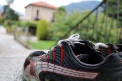 Metta in mostra le scarpe con la casa ed il giardino nel fondo Fotografie Stock Libere da Diritti