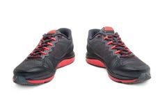 Metta in mostra le scarpe da tennis nere per correre isolato su bianco Fotografia Stock