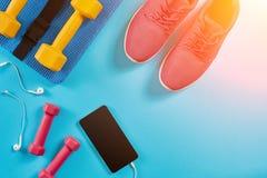 Metta in mostra le scarpe, le teste di legno ed il telefono cellulare su fondo blu Vista superiore Forma fisica, sport e concetto immagini stock libere da diritti