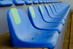Metta in mostra le sedie blu di plastica dello stadio in una fila Fotografie Stock Libere da Diritti