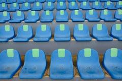 Metta in mostra le sedie blu di plastica dello stadio in una fila Fotografia Stock