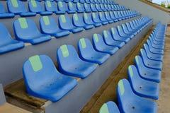 Metta in mostra le sedie blu di plastica dello stadio in una fila Immagine Stock Libera da Diritti