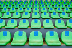Metta in mostra le sedie di plastica verdi dello stadio in una fila Immagini Stock Libere da Diritti