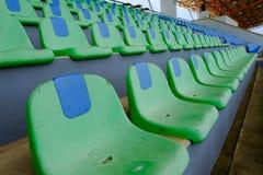 Metta in mostra le sedie di plastica verdi dello stadio in una fila Fotografia Stock