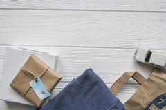 Metta nello stile del mestiere del denim con spazio per testo Il fondo di legno bianco, la borsa, vestiti, ha imballato gli ogget Immagini Stock Libere da Diritti