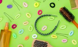 Metta per capelli che disegnano e creare le acconciature, le bugie su un fondo verde, le fasce, la gomma ed i pettini immagini stock libere da diritti