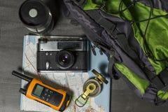 Metta per il viaggio: cartella, macchina fotografica e mappa Fotografie Stock