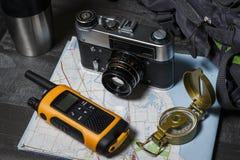 Metta per il viaggio: cartella, macchina fotografica e mappa Immagini Stock Libere da Diritti