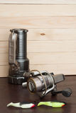 Metta per la pesca sui precedenti dei bordi Esca di plastica molle (di legno), bobina, torcia elettrica Immagine Stock