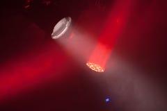 Metta in scena le luci del punto con i fasci rossi in fumo Fotografia Stock