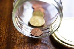Metta in serbo di euro monete greche in un barattolo Fotografia Stock Libera da Diritti