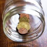Metta in serbo di euro monete greche in un barattolo Immagine Stock Libera da Diritti