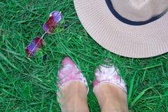 Metta sull'erba, sulle gambe del ` s delle donne in scarpe, sui vetri sotto forma di cuore e su un cappello fotografie stock libere da diritti
