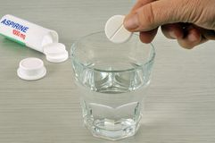 Metta un bollo di aspirin in un bicchiere d'acqua immagini stock