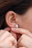 Mettant des boucles d'oreille en fonction Photographie stock libre de droits