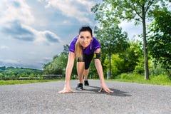 Mette in mostra all'aperto - giovane donna che fa la forma fisica in parco Immagini Stock