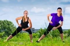 Mette in mostra all'aperto - giovani donne che fanno la forma fisica in parco Immagini Stock