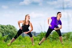 Mette in mostra all'aperto - giovani donne che fanno la forma fisica in parco Immagine Stock Libera da Diritti