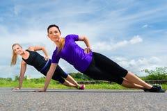 Mette in mostra all'aperto - giovani donne che fanno la forma fisica in parco Fotografia Stock