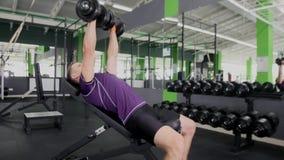 Mette in mostra l'allenamento duro dei muscoli di addestramento del giovane del culturista in palestra Fotografia Stock
