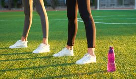 Mette in mostra la bottiglia dei piedi del ` s dell'atleta e dell'acqua sui raggi del prato inglese di mattina di luce caldi Spor fotografia stock libera da diritti