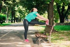 Mette in mostra la donna che allunga le gambe nell'area urbana Immagini Stock