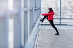 Mette in mostra la donna che fa l'allungamento all'aperto Immagine Stock