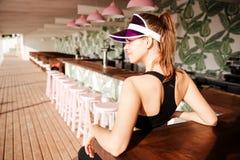 Mette in mostra la donna che riposa dopo l'allenamento in un caffè della spiaggia Fotografia Stock Libera da Diritti