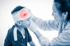 Mette in mostra la ferita Medico fa una fasciatura sul paziente capo, su bianco Fotografia Stock