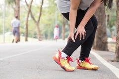 Mette in mostra la ferita spasmo Donna che tiene il muscolo irritato della gamba mentre joggin fotografia stock
