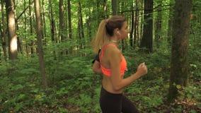 Mette in mostra la foresta corrente della donna adorabile sulla strada in cuffie, vista laterale stock footage