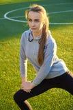 Mette in mostra la ragazza che fa l'allenamento della ginnastica di mattina su erba verde Nel controllo di luce solare calda Form Fotografia Stock