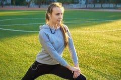 Mette in mostra la ragazza che fa l'allenamento della ginnastica di mattina su erba verde Nel controllo di luce solare calda Form Fotografie Stock
