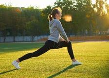 Mette in mostra la ragazza che fa l'allenamento della ginnastica di mattina su erba verde Nel controllo di luce solare calda Form Immagini Stock