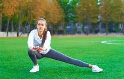 Mette in mostra la ragazza che fa l'allenamento della ginnastica di mattina su un campo di football americano Forma fisica, sport Immagine Stock Libera da Diritti