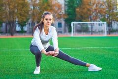 Mette in mostra la ragazza che fa l'allenamento della ginnastica di mattina su un campo di football americano Forma fisica, sport Fotografia Stock Libera da Diritti