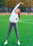 Mette in mostra la ragazza che fa l'allenamento della ginnastica di mattina su un campo di football americano Forma fisica, sport Fotografie Stock Libere da Diritti