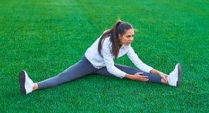 Mette in mostra la ragazza che fa l'allenamento della ginnastica di mattina su un campo di football americano Forma fisica, sport Fotografia Stock