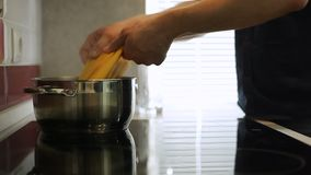 Mettendo alcuni spaghetti in un vaso di acqua bollente archivi video