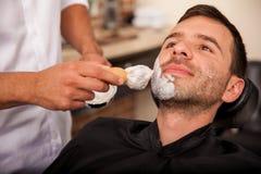 Mettendo crema da barba sopra fotografia stock