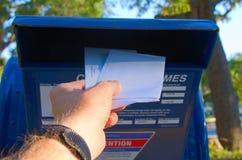 Mettendo le lettere in una cassetta delle lettere all'aperto del metallo fotografia stock libera da diritti