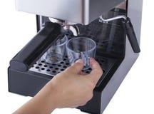 Mettendo le tazze di caffè sul vassoio del gocciolamento di macchina di caffè espresso, fasi di caffè che fanno, isolate sul fond Fotografia Stock