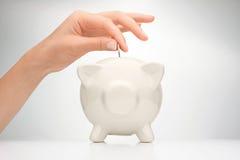 Mettendo moneta nella banca piggy Fotografia Stock Libera da Diritti