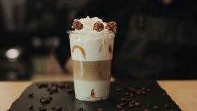 Mettendo panna montata sopra un cocktail del caffè Decorazione con il popcorn del cioccolato e versare caramello  video d archivio