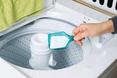 Mettendo sapone nella lavatrice Immagine Stock